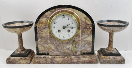 A FRENCH MARBLE GARNITURE CLOCK SET, the clock having arch top case in the Art Nouveau style, circular white enamel dial with Arabic numerals, inscribed Paris, the 8-day striking movement inscribed H & C Paris 1114, casing of polished rouge marble with black veined marble detail, clock 25cm high, flanked by a pair of shallow bowl vases on stems and squared bases