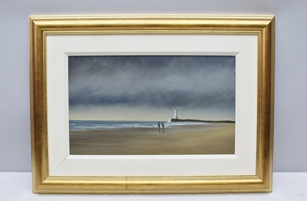 LAWRENCE COULSON Lighthouse, beach with two figures walking with umbrellas, Oil painting on board, signed, 30cm x 50cm, in gilt frame, bears Halcyon Gallery label to reverse