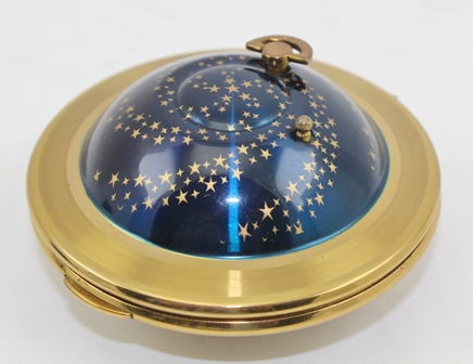 A KIGU 1950s FLYING SAUCER POWDER COMPACT blue enamelled with gilt stars, having a musical movement, with original sieve and puff, in drawstring bag, 7cm diameter (The first Kigu was created by Gustar Kiashek who had a factory in Budapest, madethe Flying Saucers from 1951, ceased manufacture in the late 1950s)