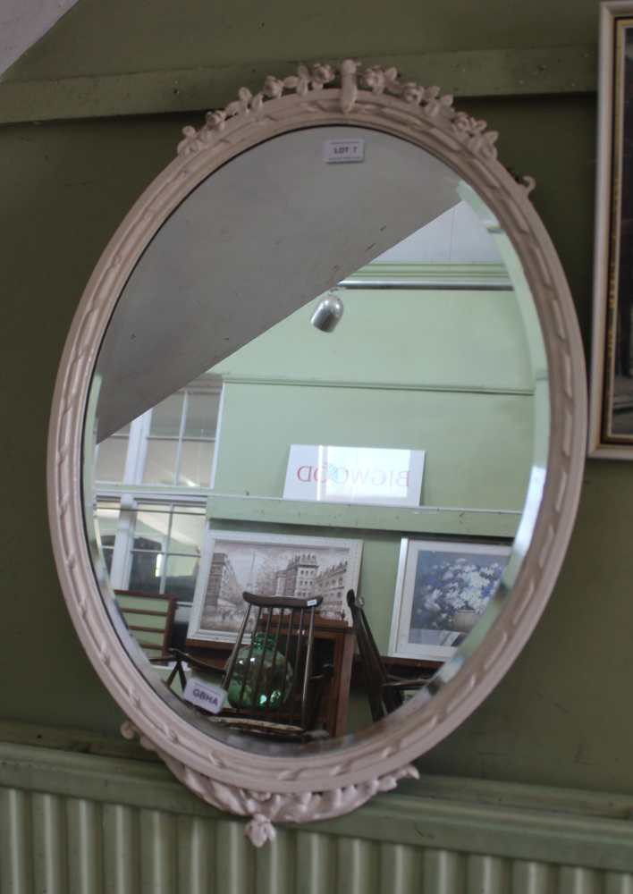 A LATER WHITE PAINTED FANCY FRAMED OVAL BEVEL