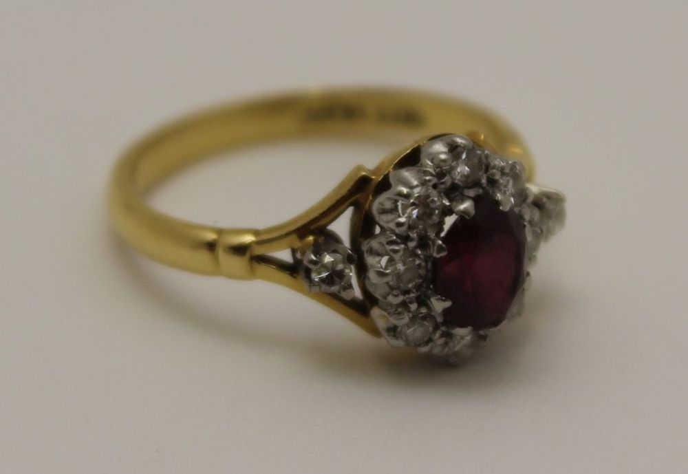 AN 18CT GOLD RUBY RING, the central stone sur