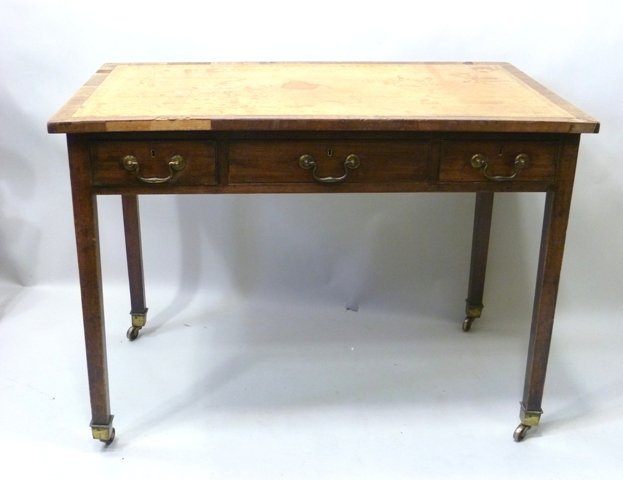 A PART 19TH CENTURY MAHOGANY SIDE TABLE, having later leather inset top with crossbanded surround, over three drawers with bale handles, raised on four square tapered legs with brass square cup castor terminals, 78cm x 107cm