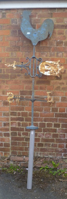 A WROUGHT IRON WEATHER VANE having a cockerel to the top in sheet steel and fretted arrow below, fleur de lys to North, 1.55m above pole