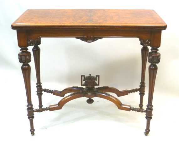 A MID VICTORIAN WALNUT FIGURED AND VENEERED TEA TABLE, having foldover top with moulded edge scroll apron, raised on four turned tapered and fluted legs with octagonal patera carved terminals, united by a shaped cross frame stretcher with urn base, 72cm x 81cm