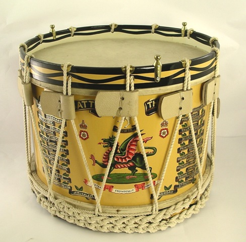 A REPRODUCTION TENOR DRUM inscribed The Buffs with roped and painted surround, inscribed Battalion The Buffs, fitted with three brass nodes for a glass top and use as a table