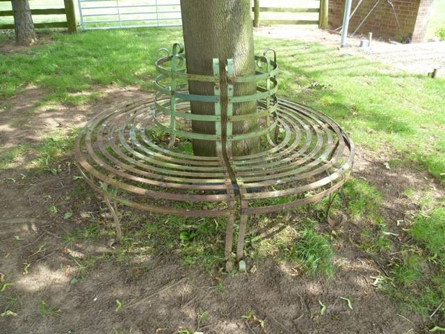 A REGENCY STYLE WROUGHT IRON CIRCULAR TREE SEAT, constructed in two halves, with painted metal slatted seat and back 1.8m diameter