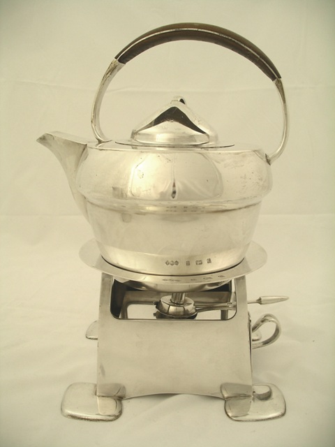 LIBERTY & CO.  AN ART NOUVEAU CYMRIC SILVER KETTLE ON STAND, the kettle having a timber mounted up-over handle, hinged lid with loop handle, on waisted body, the stand with circular flange top, squared, London 1898 body, removable burner and four squared feet, kettle 800g, stand and burner 960g (photographed marks indicate Birmingham, 1902)