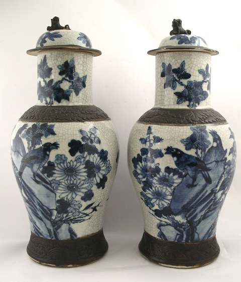 A PAIR OF LATE 20TH CENTURY ORIENTAL VASES AND COVERS, each having detachable dome lid, brown banded neck and base with underglazed blue and white bird and floral decoration, 48cm high