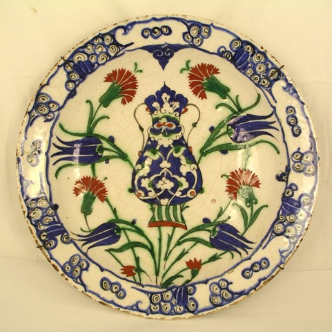 AN ANTIQUE IZNIK POTTERY DISH (believed c. 1600), having enamelled vase and floral pattern in the Persian taste, with swirling cloud border, 31cm diameter