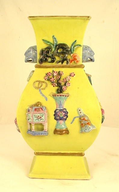 A POSSIBLY EARLY 19TH CENTURY HUNDRED ANTIQUES PATTERN CHINESE VASE with embossed yellow glazed body, having hand painted applied mouldings of Precious Things and bird head handles, the interior having turquoise glaze, 37.5cm high