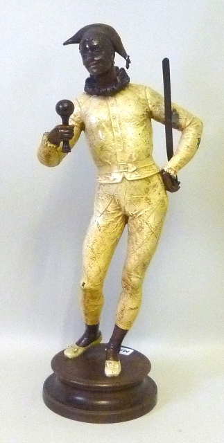 A LATE 19TH/EARLY 20TH CENTURY CONTINENTAL MODEL OF A BLACK HARLEQUIN JESTER standing jauntily holding a rattle, on circular integral base plinth, later painted, 53cm high