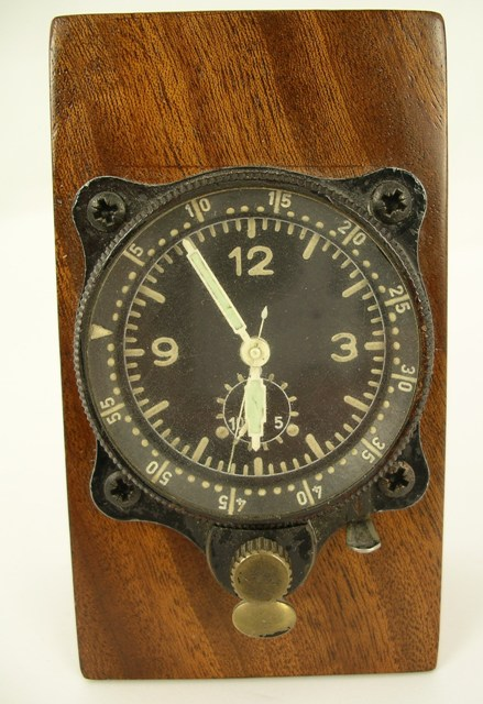 A JUNGHANS COCKPIT TIMEPIECE purportedly from a Messerschmitt 109, having luminous hands, centre seconds and Arabic quarters, on mahogany block