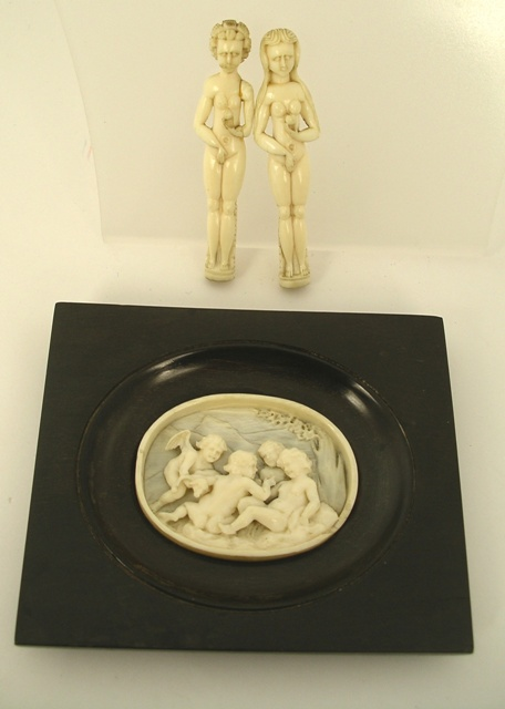 A PAIR OF EARLY 19TH CENTURY CARVED CONTINENTAL IVORY FIGURES, Adam and Eve, 83mm high, together with a carved oval IVORY RELIEF OF PUTTI beside a tree, in lignum vitae oval recessed frame, 10cm x 12cm