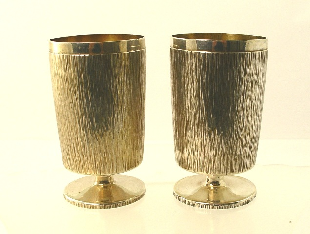 GERALD BENNEY A PAIR OF SILVER GOBLETS each of cylindrical form, bark textured , on circular pedestal base, London 1973, 486g