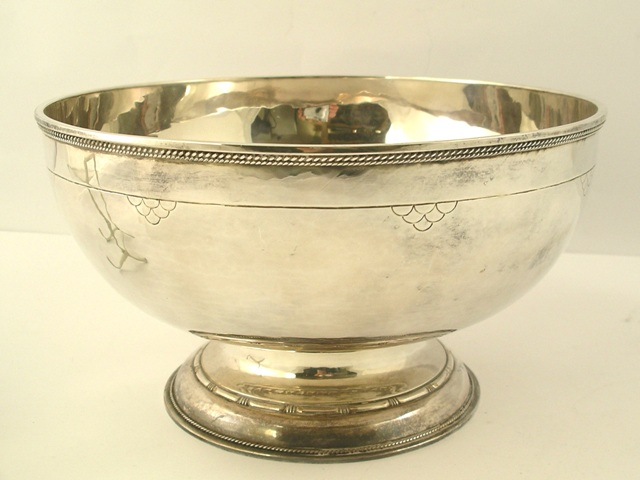 GUILD OF HANDICRAFT AN ELEVATED SILVER FRUIT BOWL having applied fancy wire rim, line engraved with motifs, on a moulded style pedestal foot, London 1930, 1048g