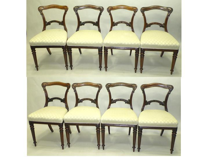 A SET OF EIGHT VICTORIAN SIMULATED ROSEWOOD ON MAHOGANY DINING CHAIRS, each having a fancy scroll carved crest rail and splat, overstuffed seat, raised on turned reeded forelegs, all standard