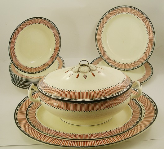A WEDGWOOD EARTHENWARE PART DINNER SERVICE having a red and black border with loop and dots, comprising; 10 x 25cm diameter soup, large oval lidded pedestal tureen, 2 oval serving platters and 2 plates x 31cm diameter