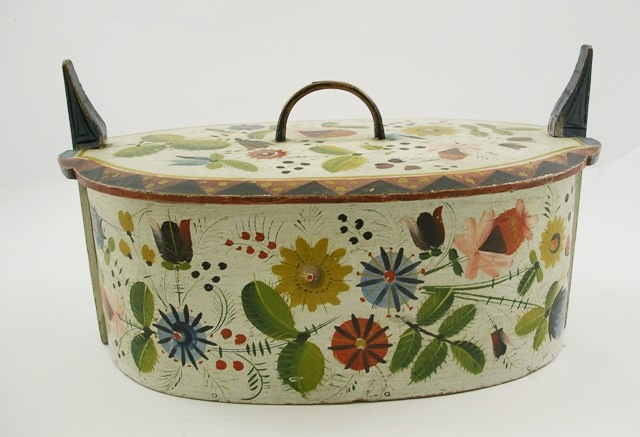 A SCANDINAVIAN/NORWEGIAN OVAL PAINTED SOFTWOOD BOX having detachable lid with loop handle and upswept clips to the ends, all over painted in multi-colours with flowers and foliage in stylised forms, possibly 19th century, 22cm x 38m