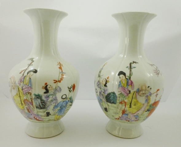 A PAIR OF 20TH CENTURY CHINESE PORCELAIN BALUSTER VASES each having a trumpet head, vertical channelled body painted with figures in polychrome, and bearing Qianlong mark stamp to base,38cm high