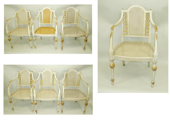 A SET OF SEVEN EARLY 20TH CENTURY CARVED AND PAINTED SOFT WOOD BERGERE ARMCHAIRS, each having a cane back with flank ring roundels, twin swept arms, a cane seat with seat pad, raised on turned and lobed forelegs