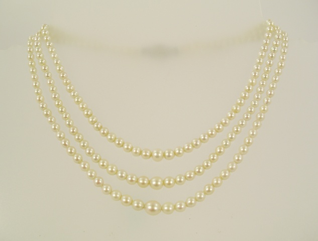 A GRADUATED THREE-ROW CULTURED PEARL CHOKER NECKLET with diamond clasp in rub over and claw setting, 32cm long