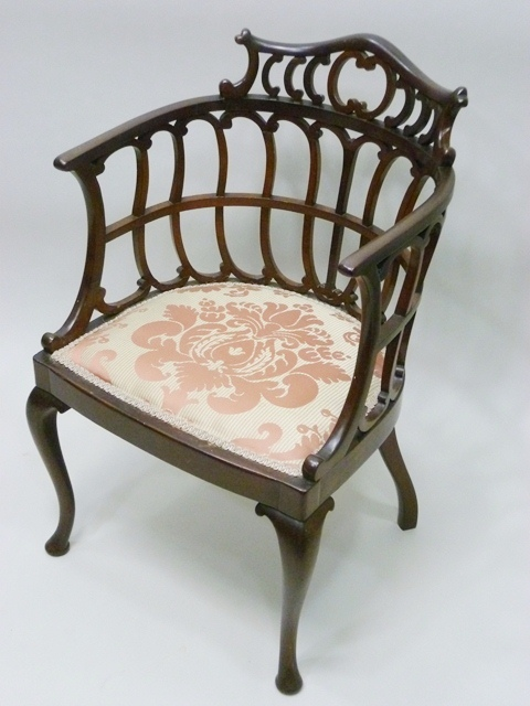 AN EARLY 20TH CENTURY MAHOGANY PARLOUR CHAIR having fretted and shaped tub back, upholstered seat, raised on cabriole forelegs