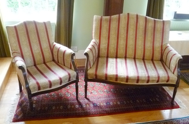 A 1920's MAHOGANY REGENCY STYLE TWO PERSON SETTEE upholstered in a period style stripe with show wood forearm supports, fluted serpentine apron, raised on turned, tapered and fluted forelegs and matching ARMCHAIR