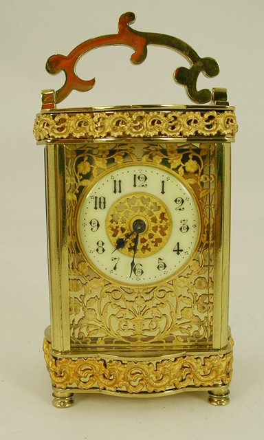 AN EARLY 20TH CENTURY GILT BRASS CARRIAGE TIMEPIECE, having scroll handle, ornate fretted top and base with serpentine front, gilt brass mask Arabic chapter, 8-day mechanism with replacement Swiss platform lever escapement and key