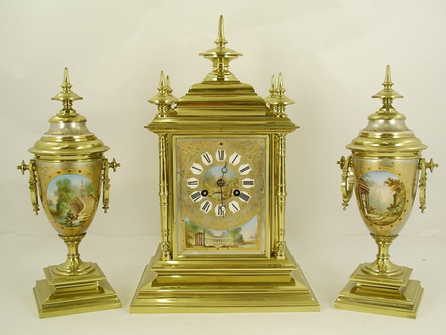 A 19TH CENTURY FRENCH BRASS CLOCK GARNITURE, the clock with five turned finial four-ringed pilasters, three French porcelain panels, each with classical garden scenes on plinth, 8-day Japy type mechanism and a pair of matching pedestal urns en suite, the mechanism with pendulum and rack bell strike and key, clock 40cm high