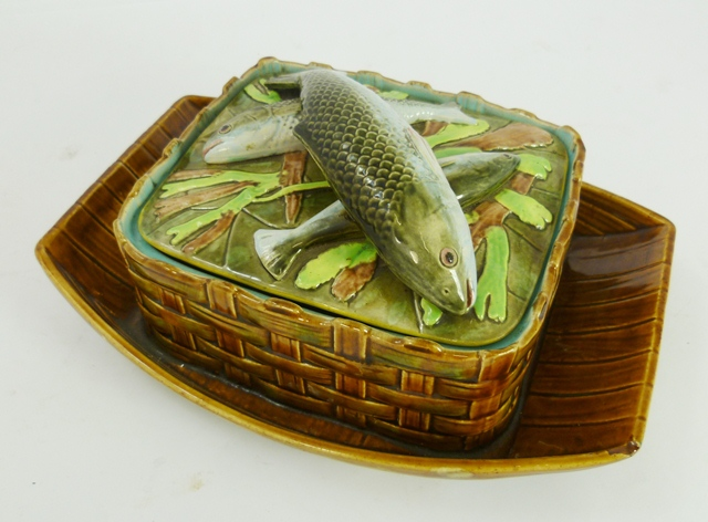 PROBABLY GEORGE JONES A VICTORIAN MAJOLICA SARDINE DISH AND COVER, the lid moulded with three fish and kelp, unmarked, the base with basket weave surround and integral tray base, bears patent office design registration raised  moulded mark and painted 3667 IIII in a scratched area underside