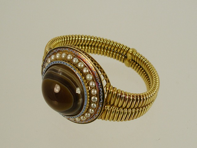 A VICTORIAN ETRUSCAN STYLE GOLD BRACELET the centre set with chocolate cabochon agate bordered by enamel and seed pearls on a wire frame with bendy gold bracelet, total weight 58g, Cabochon approximately 27mm diameter