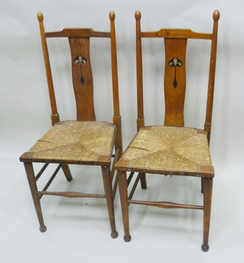 WILLIAM BIRCH A PAIR OF COTSWOLD ARTS & CRAFTS CHAIR each having ash turned uprights with bulb finials, inlaid splat rush seat, raised on tapered forelegs united by a rance