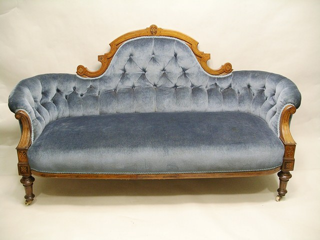 A MID VICTORIAN WALNUT AND BOXWOOD INLAID SHOW WOOD FRAMED SETTEE having shaped back with inlaid motifs and stringing, blue velveteen button upholstery and overstuffed seat, raised on turned and inlaid forelegs with white ceramic castors