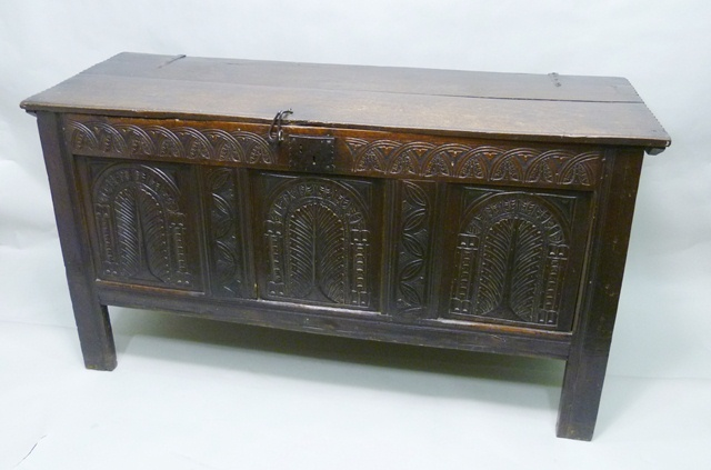 A LATE 17TH CENTURY ENGLISH OAK COFFER with later alterations, having later plank top with adzed edge, older carved tri-panel front with arch arboreal motifs below later carved top panel, raised on four long stile feet, no candle box, 84cm x 1.55m