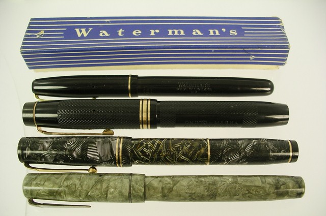 A SELECTION OF FOUR FOUNTAIN PENS: a De La Rue Onoto Magna in black vinyl and nib stamped 14k, a Swan Visofil in green marbled finish, nib stamped Mabie Todd 14k, a Swan Self Filler green marbled, and a Waterman's black vinyl W2 in original vending box