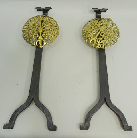A PAIR OF BRASS AND WROUGHT STEEL FIRE DOGS having pierced brass shields and steel supports, 54cm high