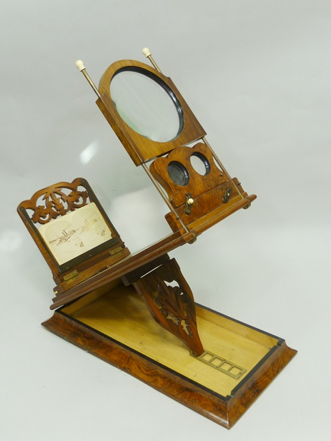 A WALNUT DESK TOP STEREOSCOPIC VIEWER having adjustable ratchet and magnifying lens, together with a collection of photographic stereoscopic slides, 52m wide, contained within a mahogany box