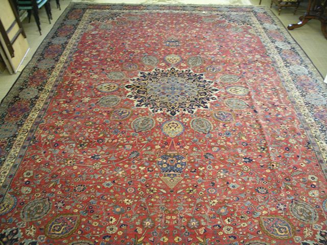 A 20TH CENTURY PERSIAN CARPET being a copy of The Ardebil Carpet, after the example in the V & A Museum, having  book cover centre with two different sized mosque lamps on a madder field, within a four guard border, containing a signature panel, approximately 4m x 6m