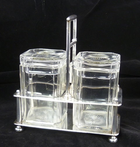 ELKINGTON & CO. AN ART DECO SILVER AND LEAD CRYSTAL DOUBLE JAM/PRESERVE POT, having twin square and canted stoppered glass pots, in a wire work frame on bun feet, Birmingham 1901, 896g.