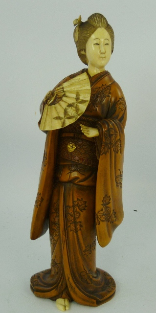AN EARLY 20TH CENTURY JAPANESE CARVED WOOD AND IVORY OKIMONO of a girl holding a fan, 28cm high