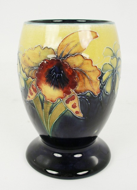 WALTER MOORCROFT AN EARTHENWARE VASE of ovoid form, having yellow and blue ground decorated with anemones and iris, 15cm high