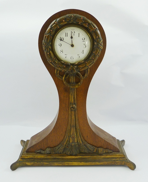 A LATE 19TH CENTURY FRENCH OAK AND ORNATE CAST GILT METAL MOUNTED MANTEL TIMEPIECE having broad balloon outline having cast and applied foliate surround and tassels, on four bead plinth, 8-day mechanism with platform cylinder escapement, faced by Arabic enumerated enamel dial, 42cm high
