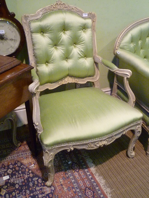 A PAIR OF 20TH CENTURY PAINTED SHOW WOOD FRAMED FRENCH STYLE FAUTEUILS, each having green silk button back, overstuffed seat with carved apron and raised on cabriole forelegs