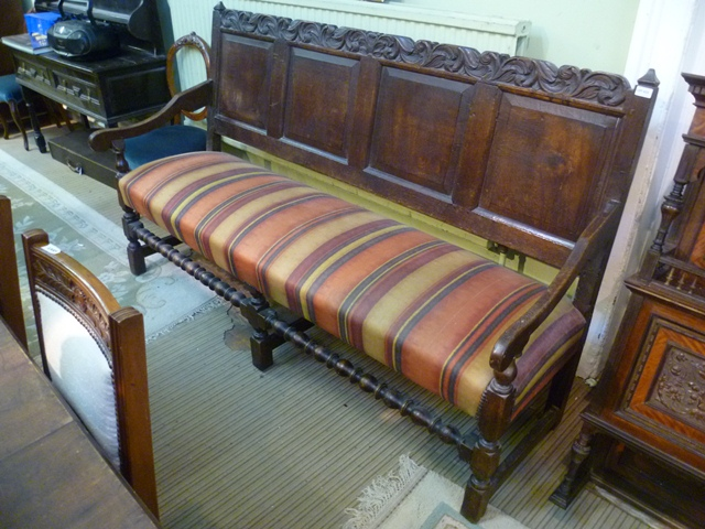 A PART 19TH CENTURY RUSTIC STYLE OAK BENCH SETTLE having carved frieze over four fielded panel back, twin flank arms, modern striped upholstered seat, raised on six turned and blocked legs united by a bottom turned stretcher