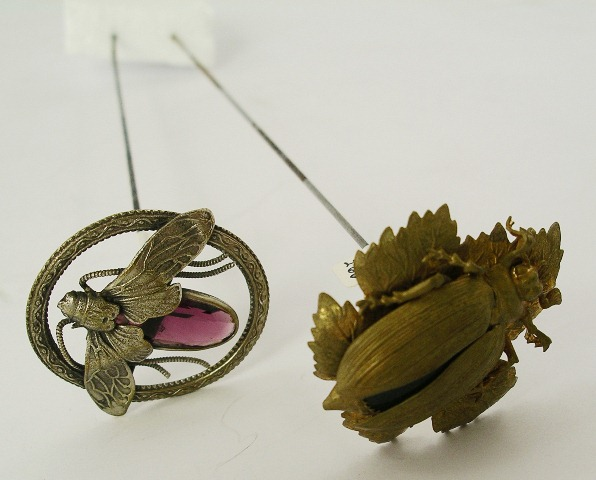 TWO HAT PINS each having large insect shaped head, one fashioned as a beetle in gilt metal with green stone body, the other fashioned as a fly with facetted amethyst colour body