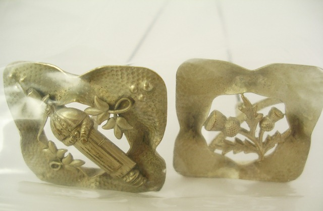 A MATCHED PAIR OF WHITE METAL HAT PINS, each having fretted and tooled square head, one with a Welsh figure, the other with a Scottish thistle