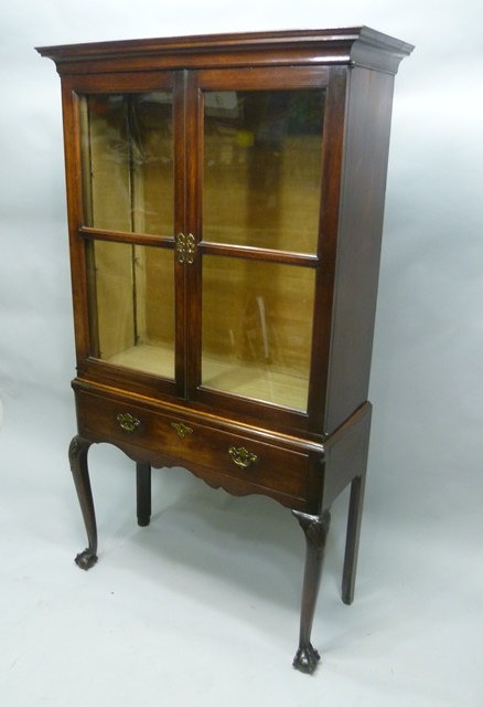 A 19TH CENTURY GEORGIAN STYLE OAK SIDE CABINET ON STAND, (with later alterations)  the upper detachable section with moulded pediment and twin glazed doors opening to reveal three glass shelves, on a base with drawer, cabriole forelegs, scallop carved knees terminating in talon and ball feet, 183cm x 95cm