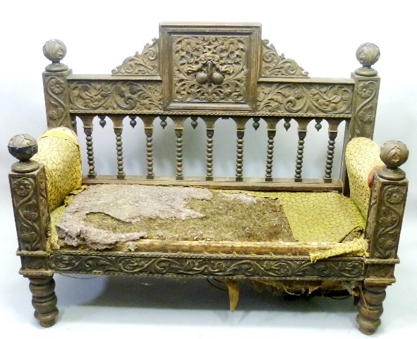 A VICTORIAN OAK FINISHED CARVED SETTLE, the back decorated with cherub and acanthus and foliage supported on bobbin uprights, remnants of upholstered arms and seat, fronted by flora carved newel style uprights, raised on bulbous turned legs, 110cm x145cm extreme