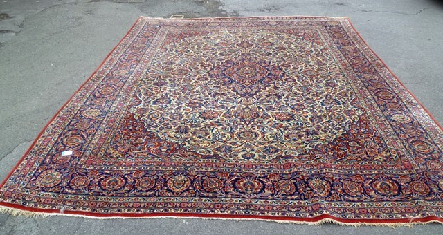 A KIRMAN CARPET having bold red, blue floral and foliate all over decoration in book cover form, 4.05m x 3.10m