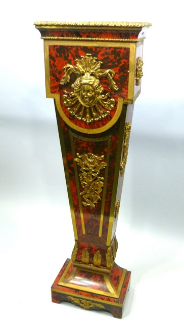 A 20TH CENTURY FRENCH LOUIS XIV STYLE SIMULATED SCARLET TORTOISESHELL BOULLE PEDESTAL, having gilt brass mounts with egg and dart motifs, facial mask, violin and other motifs, tapered body and bracket foot base, 1.42m high x 41cm wide